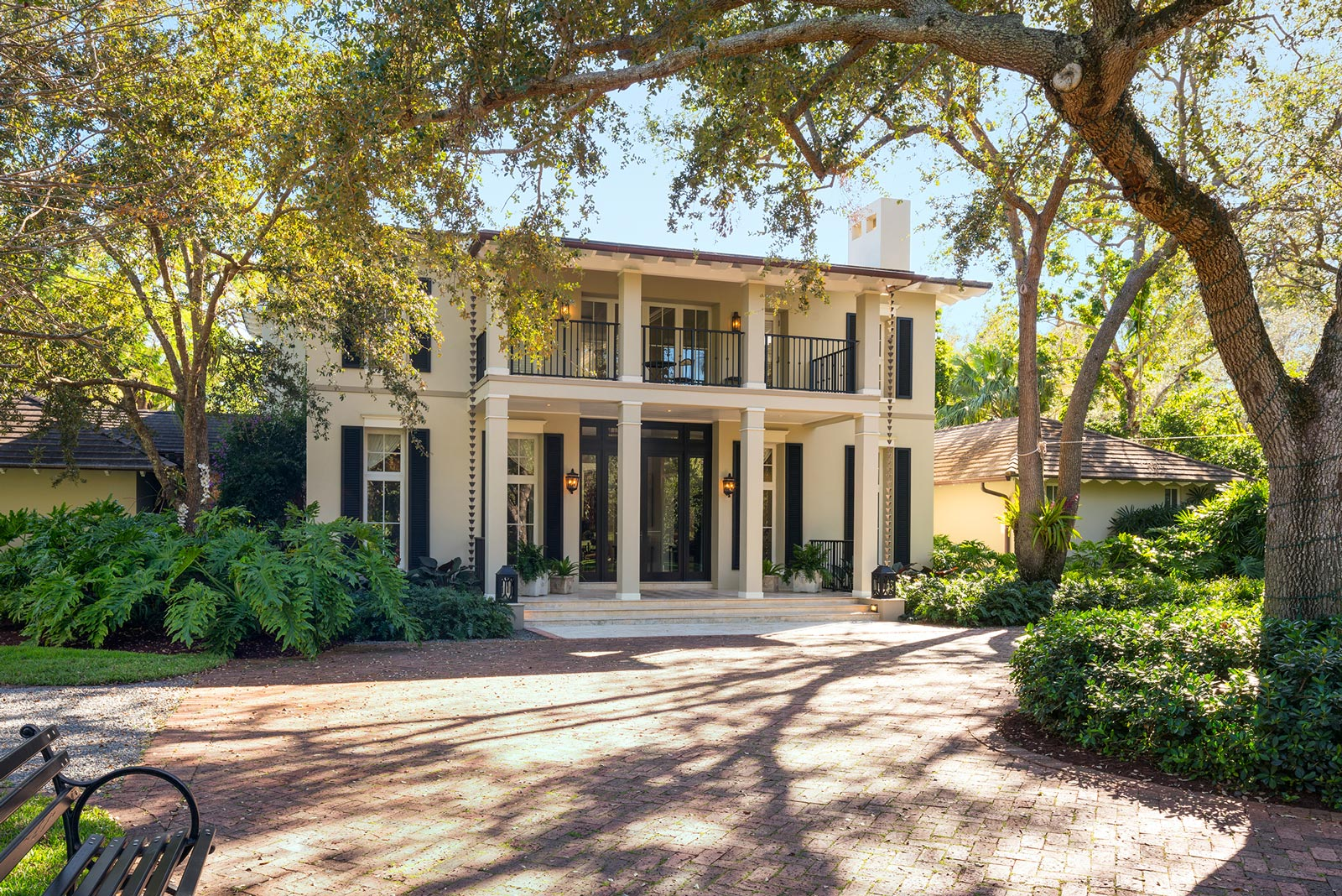 This southern style property flaunts elevated ceilings with pearly crown molding intended to enhance the two-story home's contemporary atmosphere. Lounging on the wrap-around, second-floor balcony will grant any viewer a breathtaking glimpse of the home's modern swimming court and spacious patio enveloped by towering palms trees.